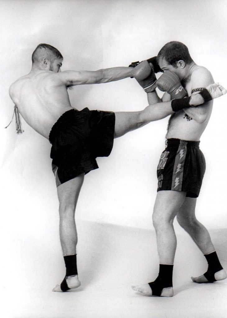 Two opponents doing Thai boxing kick and blocks